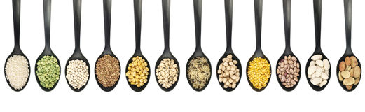 Variety of raw legumes and rices in spoons - white background. Variety of raw legumes and rices in spoons on white background Stock Photo