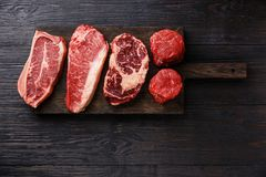 Variety of Raw Prime meat steaks. Variety of Raw Black Angus Prime meat steaks Blade on bone, Striploin, Rib eye, Tenderloin fillet mignon on wooden board copy Stock Image