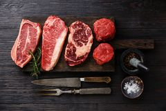 Variety of Raw Prime meat steaks. Variety of Raw Black Angus Prime meat steaks Blade on bone, Striploin, Rib eye, Tenderloin fillet mignon on wooden board Stock Photos