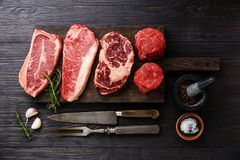 Variety of Raw Prime meat steaks. Variety of Raw Black Angus Prime meat steaks Blade on bone, Striploin, Rib eye, Tenderloin fillet mignon on wooden board Stock Image