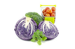 Variety of raw vegetables. Purple cabbage, cherry tomatoes on trolley, green mint and broccoli  white background Stock Images