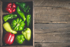 Variety red and green bell peppers of various shapes. Full vegetable tray On a wooden background Royalty Free Stock Image