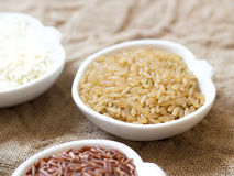 Variety of rice in bowls on wooden table Stock Photos