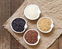 Variety of rice in bowls on wooden table Royalty Free Stock Photos