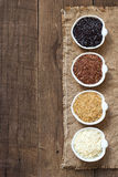 Variety of rice in bowls on wooden table Royalty Free Stock Photo