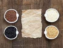 Variety of rice in bowls on wooden table and old paper Royalty Free Stock Photo