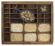 Variety of rice grains in vintage drawer. Variety of rice grains (white, brown, black, forbidden, wild, basmati, arborio, short, long grain) in vintage wooden Royalty Free Stock Photo