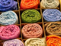 Variety of rolled silk scarves of different vivid colours stock photo