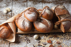 Variety of rye bread on a wooden background. With flour, grain and quail eggs Stock Photography