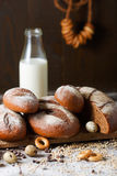 Variety of rye bread on a wooden background with. Milk, a bundle of bagels, flour, grain and quail eggs Royalty Free Stock Image