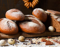 Variety of rye bread on a wooden background with. Milk, a bundle of bagels, flour, grain and quail eggs Royalty Free Stock Photography