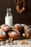 Variety of rye bread on a wooden background with. Milk, a bundle of bagels, flour, grain and quail eggs Stock Image