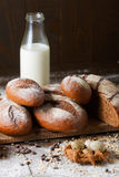 Variety of rye bread on a wooden background with. Milk, a bundle of bagels, flour, grain and quail eggs Stock Photos
