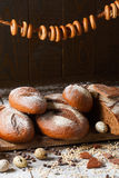 Variety of rye bread on a wooden background with. Milk, a bundle of bagels, flour, grain and quail eggs Royalty Free Stock Images