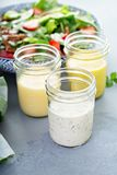 Variety of salad dressings in glass jars. With ranch, italian and honey mustard royalty free stock photography