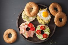 Variety of sandwiches on bagels: egg, avocado, ham, tomato, soft. Cheese, alfalfa sprouts Royalty Free Stock Images