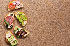 A variety of sandwiches with red fish, smoked sausage, vegetable on a brown stone background. Top view, copy space.  stock image