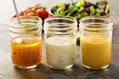 Variety of sauces and salad dressings. Variety of homemade sauces and salad dressings in mason jars including vinaigrette, ranch and honey mustard royalty free stock images