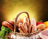Variety of sausage products in the basket over brown background. Stock Photos