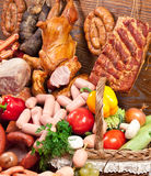 Variety of sausage products and basket with vegetables. Stock Photo