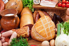 Variety of sausage products with vegetables and herbs. Stock Photography