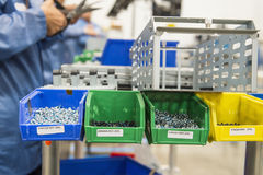 Variety of screws in tray with engineers working at electronics industry Stock Photography