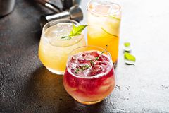 Variety of seasonal cocktails. Variety of seasonal fall cocktails with citrus, apple cider, pomegranate syrup, whiskey and gin royalty free stock photo