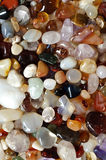 Variety of semi precious gemstones. Variety of cut semi-precious gemstones like tourmaline, rose quartz, agate, opal, jaspis, tiger eye, amethyst, jade , crystal Royalty Free Stock Images