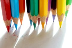 A variety of sharpened pencils stand on a piece of paper. There are colored pencils sharpened on white paper and its shadow royalty free stock image