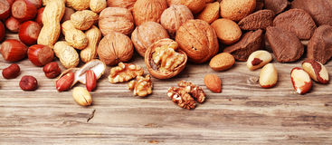Variety of shelled and whole nuts in a banner. Variety of shelled and whole nuts in a horizontal banner including almonds, hazelnuts, brazil nuts, peanuts and Royalty Free Stock Photos