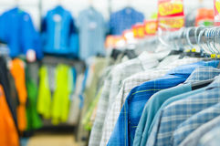 Variety of shirts and t-shirts on stands in shop Royalty Free Stock Image