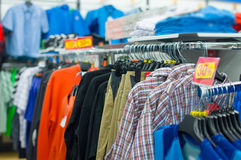 Variety of shirts, t-shirts and trousers on stands Stock Photos