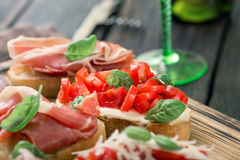 Variety small sandwiches with prosciutto, tomatoes, fresh basil Royalty Free Stock Images