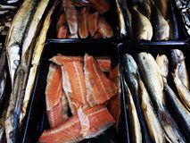 Variety of smoked fish for sale. Variety of smoked fish - needlefish, salmon file, trouts and bream fish smoked stock image