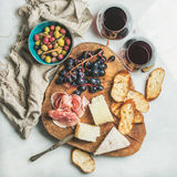 Variety of snacks and red wine in glasses, grey background Royalty Free Stock Photos