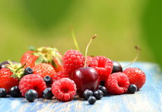 Variety of soft fruits, strawberries, raspberries, cherries, blueberries on table. In the garden Royalty Free Stock Photography