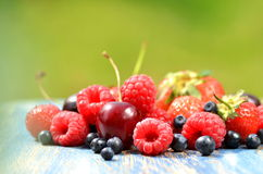 Variety of soft fruits, strawberries, raspberries, cherries, blueberries on table. In the garden Stock Image