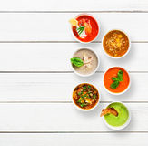 Variety of soups at white wood, top view. Variety of restaurant hot dishes, healthy food. Japanese miso, asian fish soup, russian borscht, english pea soup with Royalty Free Stock Photography