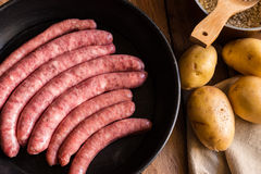 Variety of Spanish raw uncooked sausages longaniza in iron cast pan, dinner ingredients, potatoes, rice in pot Royalty Free Stock Photos