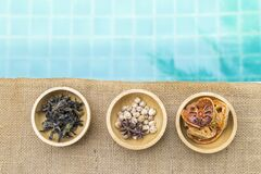 Variety of spice and herbs in wooden bowl with space on blue water background