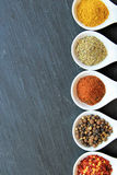 Variety of spices on a black slice Royalty Free Stock Images
