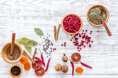 Variety of spices and dry herbs in bowls on light wooden kitchen table background top view mock-up Royalty Free Stock Photography