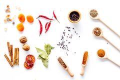 Variety of spices and dry herbs in spoons on white kitchen table background top view pattern Stock Images