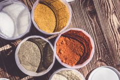 Variety of spices and herbs on kitchen table. stock images