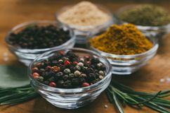 Variety of spices in round glass bowls - ground ginger, hops-suneli, kari, black pepper and mix. On a wooden table royalty free stock image
