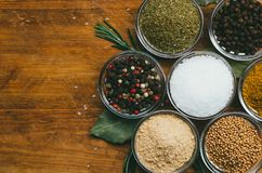 Variety of spices in round glass bowls - ground ginger, hops-suneli, kari, black pepper and mix. On a wooden table stock images