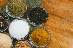 Variety of spices in round glass bowls - ground ginger, hops-suneli, kari, black pepper and mix. On a wooden table royalty free stock photography
