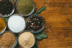 Variety of spices in round glass bowls - ground ginger, hops-suneli, kari, black pepper and mix. On a wooden table stock photography