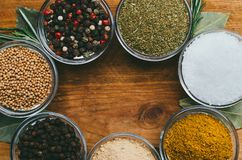 Variety of spices in round glass bowls - ground ginger, hops-suneli, kari, black pepper and mix. On a wooden table royalty free stock images