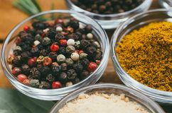 Variety of spices in round glass bowls - ground ginger, hops-suneli, kari, black pepper and mix. On a wooden table stock photo